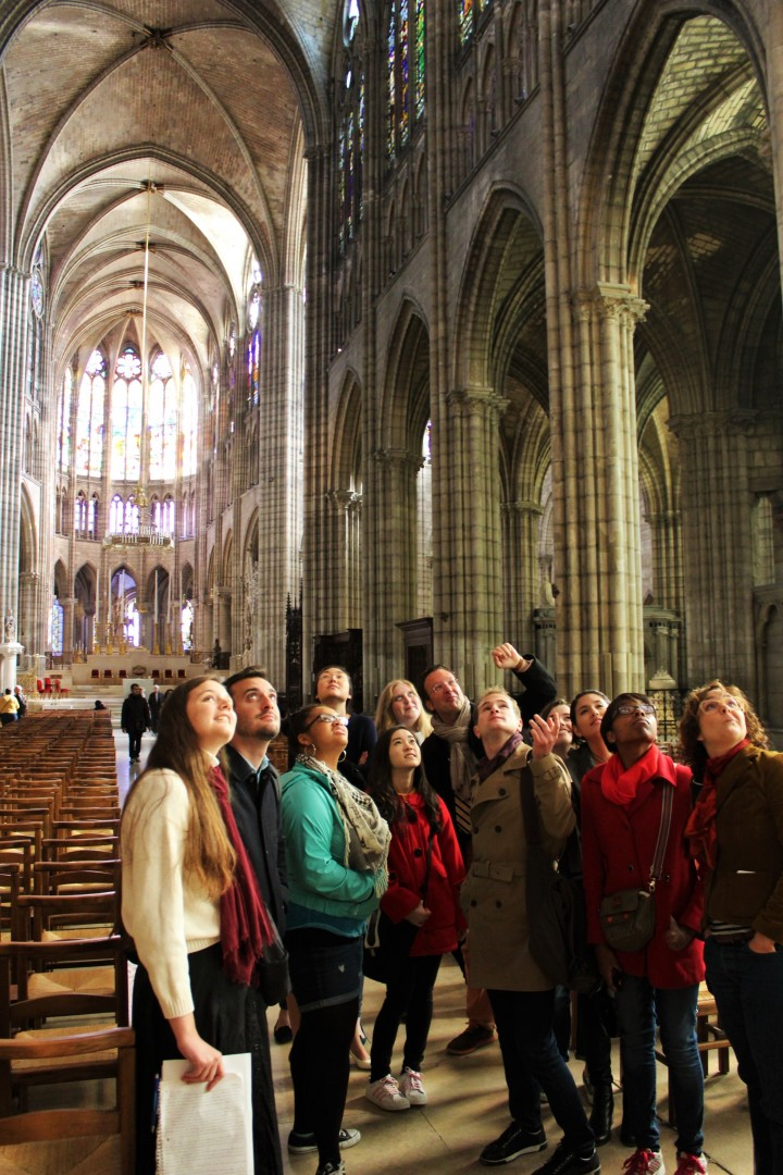 Students with professor looking up in a Gothic cathedral