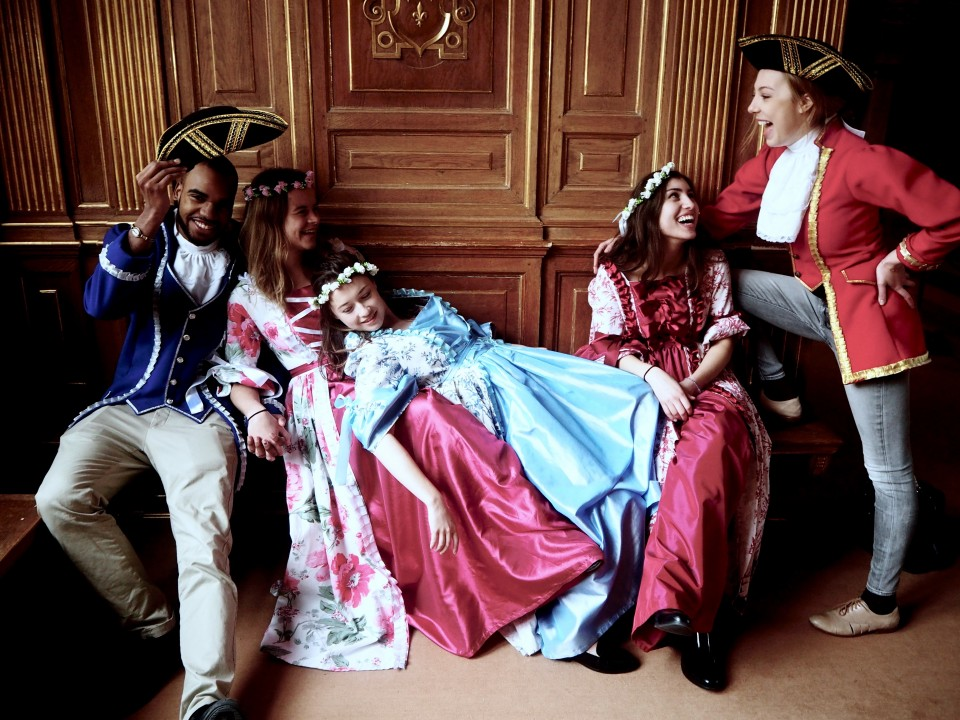 Students dressed up as royalty and sitting in a room in a castle.
