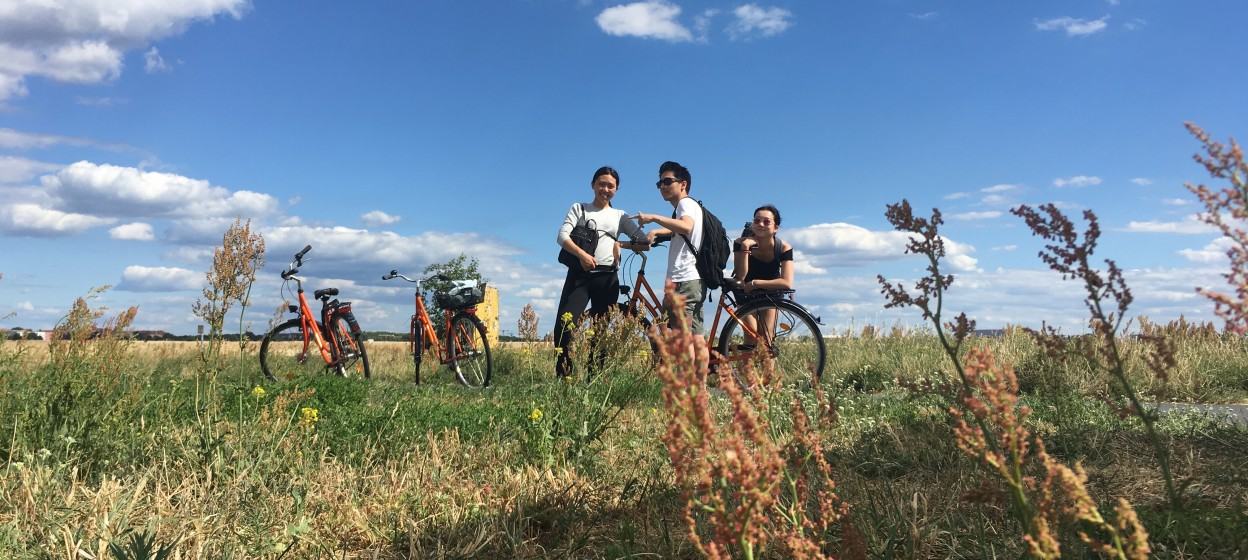 Bikes and students in a field with clouds