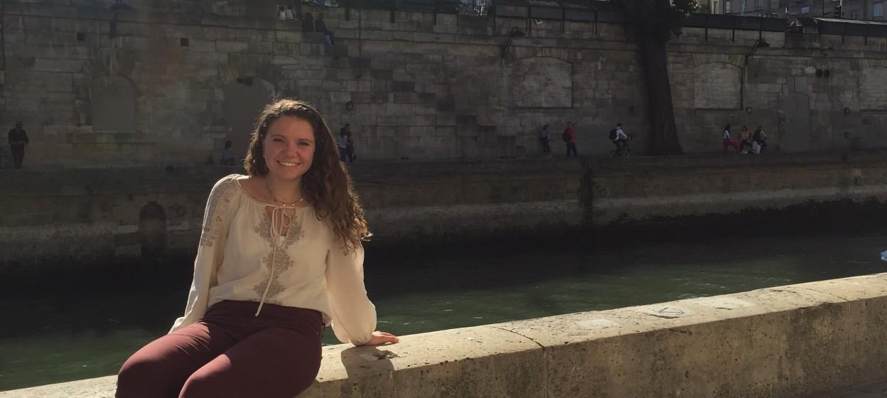 Student sitting next to the Seine in Paris