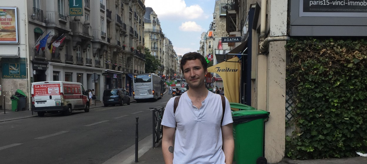 Male student standing on a street in Paris
