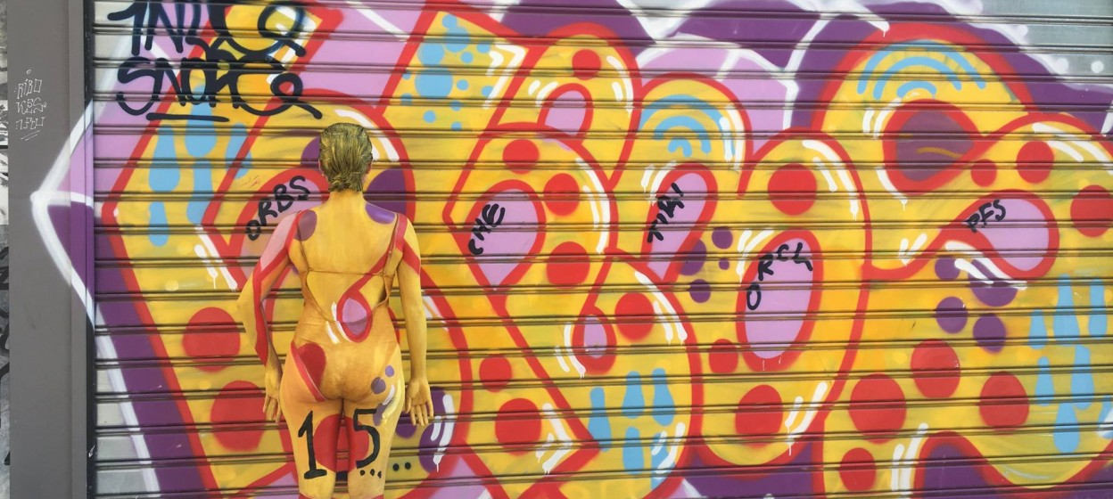Painted woman standing in front of graffiti and blending in