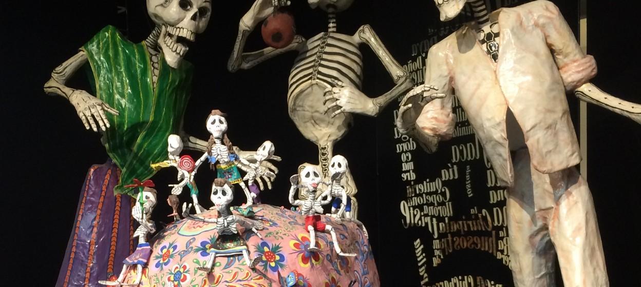 Dia de los Muertos skeletons laughing around a pink skull