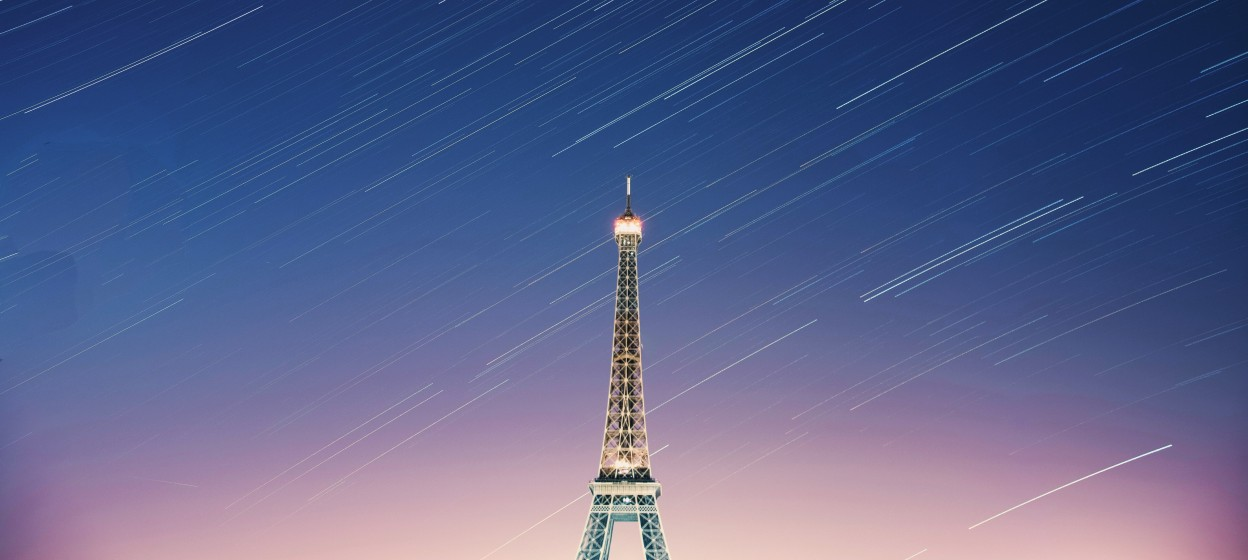 A time-lapse photo of the Eiffel Tower at sunset