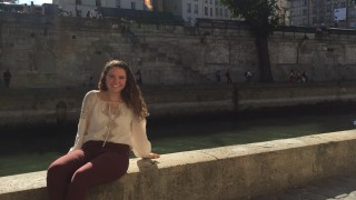 Student sitting next to the Seine in Paris